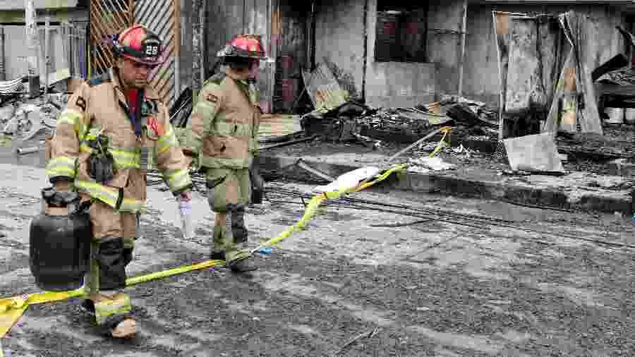 23.jan.2020 - Bombeiros caminham em frente a casas destruídas pela explosão de caminhão-tanque em Lima - AFP