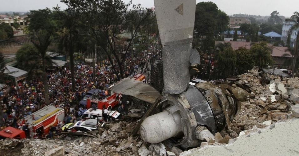 30.jun.2015 - A hélice do avião de transporte militar indonésio C-130 Hercules fica sobre telhado de um prédio após a aeronave cair em área residencial da cidade de Medan, na ilha de Sumatra, Indonésia. O acidente incendiou casas e veículos e matou mais de cem pessoas