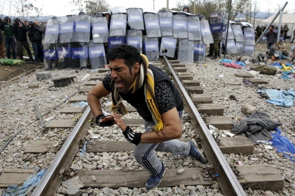 28.nov.2015 - Um refugiado lamenta em frente ao cordão policial macedônio durante um protesto contra a construção de uma cerca de quatro quilômetros de extensão na fronteira com a Grécia a fim de prevenir o cruzamento ilegal de refugiados e migrantes