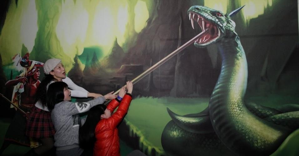 11.fev.2016 - Moradores posam com uma pintura em um shopping center em Xangai, leste da China. O trompe l'oeil  é uma técnica de arte que usa imagens realistas para criar a ilusão de objetos em três dimensões