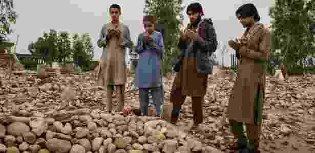 10.abr.2016 - Zia ul-Haq, segundo à direita, e três de seus irmãos, visitam cemitério onde enterraram corpo que acharam que era de seu pai, no distrito de Behsud, no Afeganistão - Adam Ferguson/The New York Times - Adam Ferguson/The New York Times