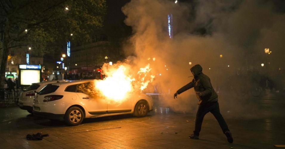 """23.abr.2016 - Manifestante lança objeto em carro incendiado na praça de la Republique, em Paris, durante protesto na sequência de um ato Nuit Debout (Noite Acordada). Os Nuit Debout, cada vez mais recorrentes na França e que protestam contra propostas do governo de reformas trabalhistas, vêm sendo reprimidos pela polícia, que acusa a presença de """"desordeiros"""" entre os manifestantes"""