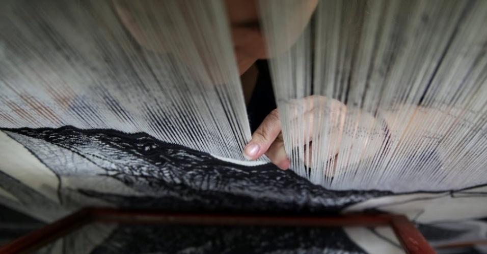 13.out.2016 - Tecelã usa espelho para verificar trabalho de tapeçaria em fábrica de tear em Madri