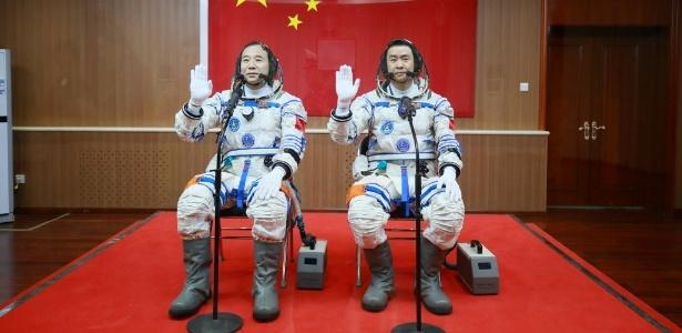 Astronautas chineses Jing Haipeng (esq) e Chen Dong posam em frente a bandeira da China