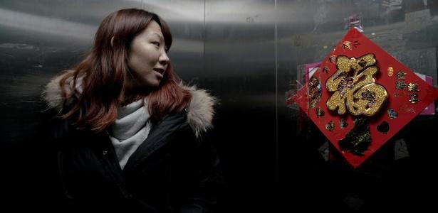 """Zhao Yuqing observa ideograma que significa """"boa sorte"""" em um quadro no elevador do prédio onde mora, em Pequim"""