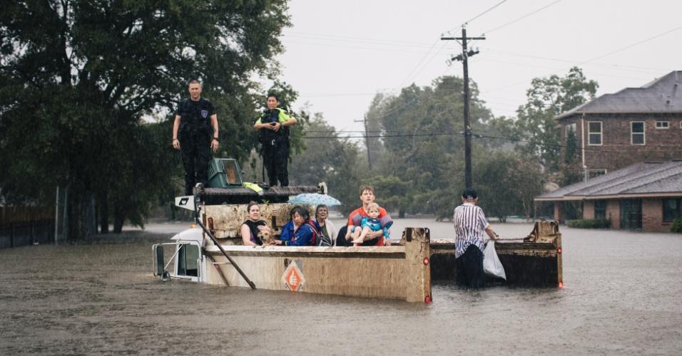 27.ago.2017 - Equipes de resgate e civis aguardam socorro em caminhão submerso pela metade em rua alagada de Houston após a passagem da tempestade Harvey