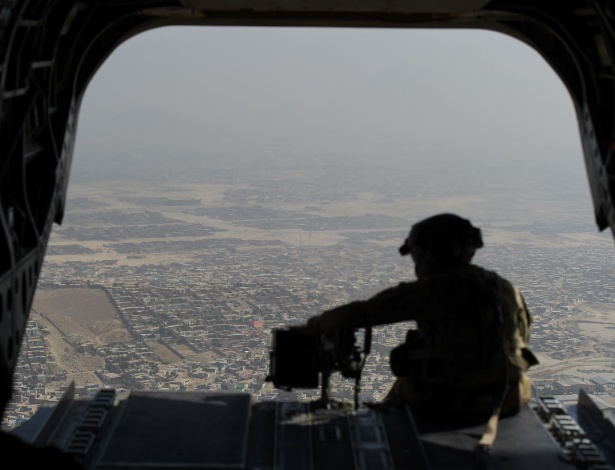 10.ago.2017 - Soldado americano senta na parte de trás de helicóptero militar durante voo sobre Cabul, no Afeganistão