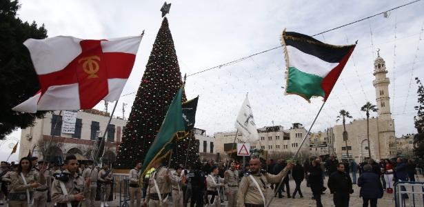 Cristãos palestinos se apresentam diante da Igreja da Natividade durante as festividades de Natal em Belém
