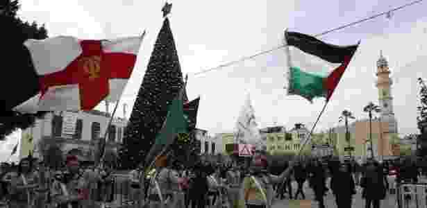 Cristãos palestinos se apresentam diante da Igreja da Natividade durante as festividades de Natal em Belém - HAZEM BADER/AFP