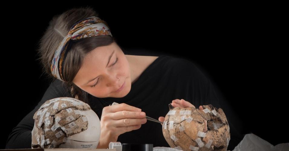 Pesquisadora analisa fóssil encontrado em sítio arqueológico sueco