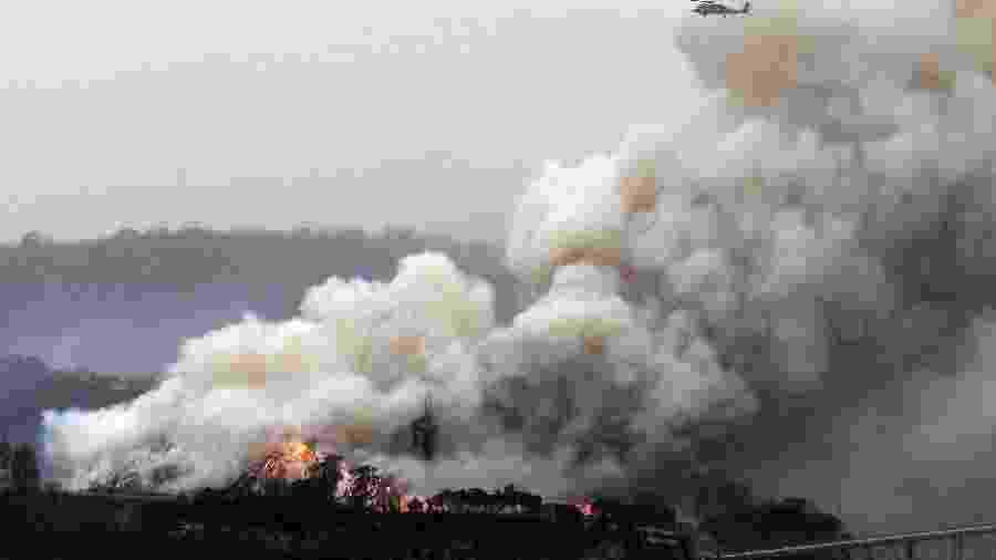 6.jan.2020 - Helicóptero militar sobrevoa incêndio florestal em Eden, Nova Gales do Sul, Austrália - Saeed Khan/AFP