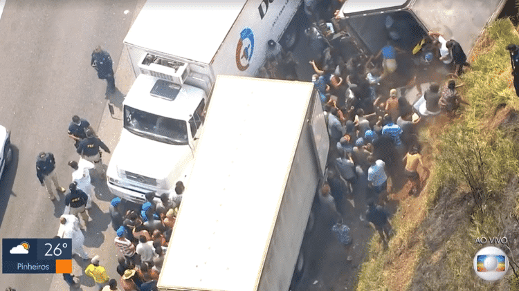 Mesmo com a presença de agentes da PRF e da GCM, pessoas continuaram sacando o caminhão tombado - Reprodução/TV Globo - Reprodução/TV Globo