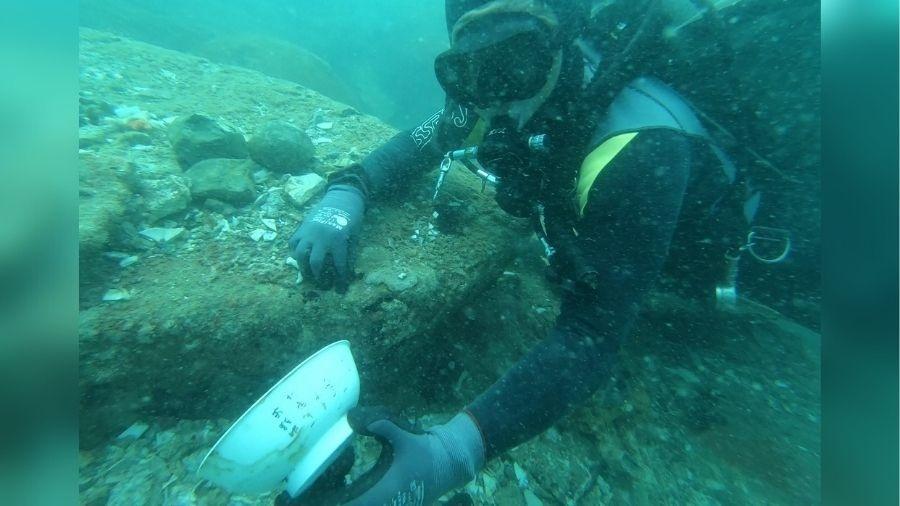 Mergulhador mostra uma das antiguidades encontradas entre escombros de embarcação - Reprodução/Facebook