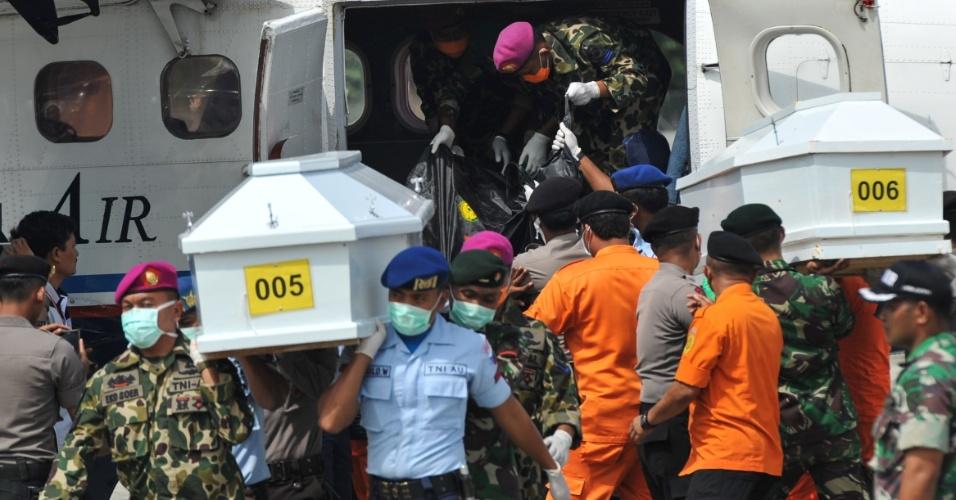 20.ago.2015 - Soldados e policiais desembarcam caixões de vítimas do avião ATR 42-300 da companhia indonésia Trigana, que caiu no último domingo e provocou a morte de 54 pessoas, na base aérea de Jayapura, na Indonésia. De acordo com as autoridades locais, todos os corpos já foram recuperados. A aeronave caiu em consequência do tempo ruim nas montanhas Bintang, uma área de selva que não tem vias de acesso por terra, a 15 km do aeroporto de Oksibil, onde deveria acontecer o pouso