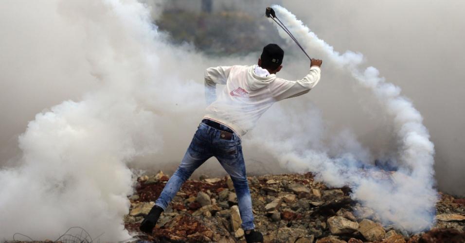 27.out.2015 - Manifestante palestino lança bomba de gás durante confrontos com as forças de segurança israelenses na entrada norte da cidade de Al-Bireh, na periferia norte de Ramallah, na Cisjordânia. Uma das piores ondas de violência de rua em anos foi iniciada em parte pela ira palestina com o que eles veem como uma invasão judaica ao complexo da mesquita de Al Aqsa, em Jerusalém, o terceiro local mais sagrado do Islã e também reverenciado pelos judeus como o local de dois templos antigos