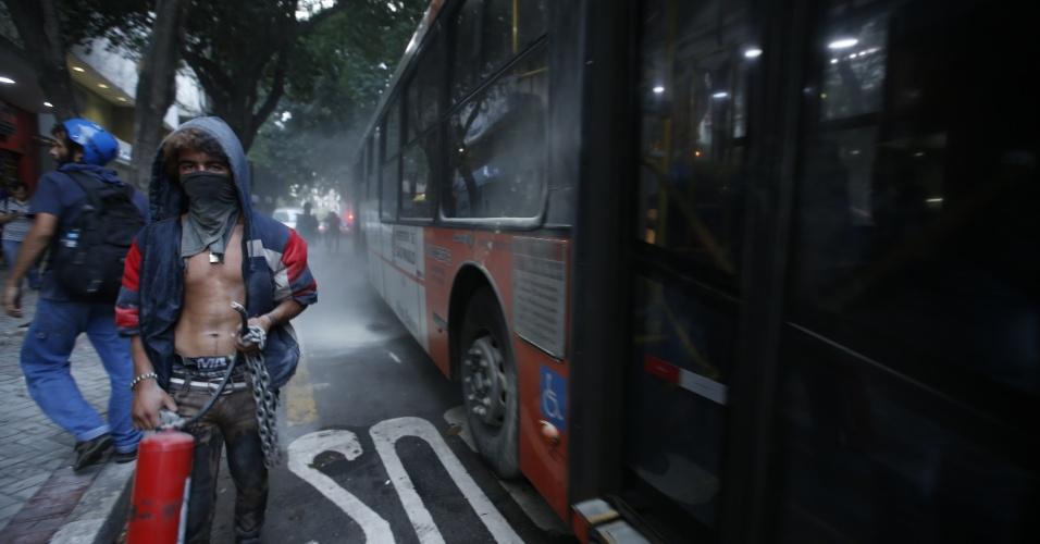8.jan.2016 - Jovem com o rosto coberto segura extintor de incêndio depois de quebrar os vidros de um ônibus durante confusão em ato contra o aumento do valor da tarifa do transporte público de São Paulo, no centro de São Paulo. Neste sábado (9), tarifa passa de R$ 3,50 para R$ 3,80