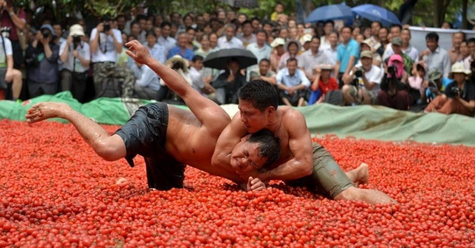 15.abr.2016 - Competidores de wrestling, luta de corpo-a-corpo, se enfrentam em uma piscina de tomates em festival em Tianyang, na China