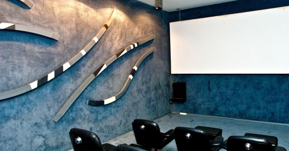 No salão para projeções, a parede é revestida com carpete acústico, em obra de Athos Bulcão feita em madeira pintada