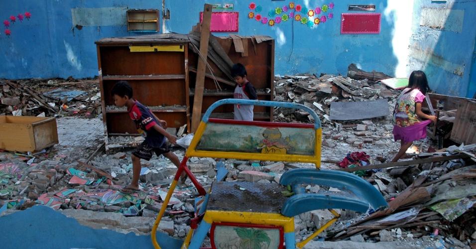 3.jun.2016 - Crianças buscam por livros e material escolar em meio aos escombros de escola na Indonésia. O imóvel desabou depois da forte tempestade que atingiu a região de Gresik nesta quinta-feira (2)