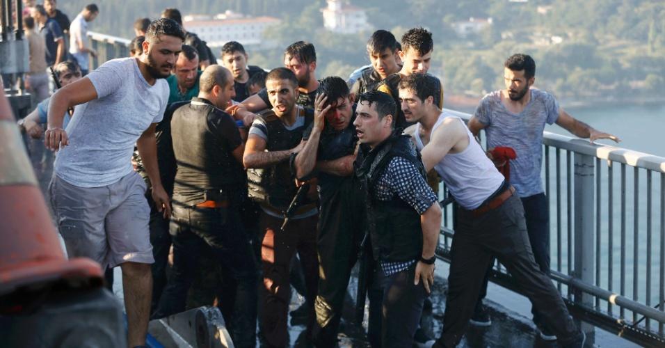 16.jul.2016 - Policiais turcos formam um cordão para proteger soldado ferido em Istambul. O soldado fez parte do grupo de militares que tentou promover um golpe de estado no país e fechou as pontes que cruzam o Estreito de Bósforo