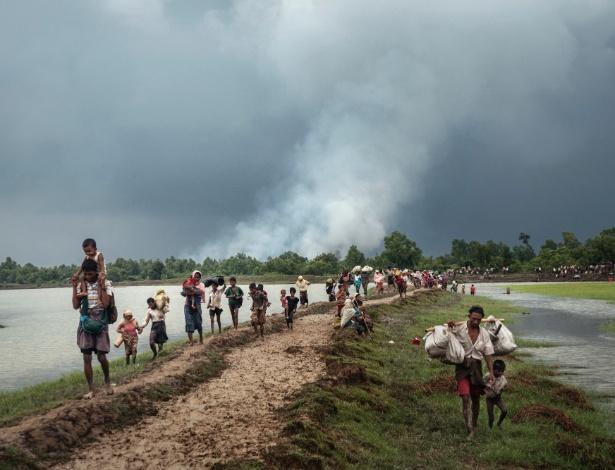 Refugiados rohingyas descansam perto do rio Naf separando Myanmar e Bangladesh depois de atravessar a fronteira, perto de Palong Khali, Bangladesh