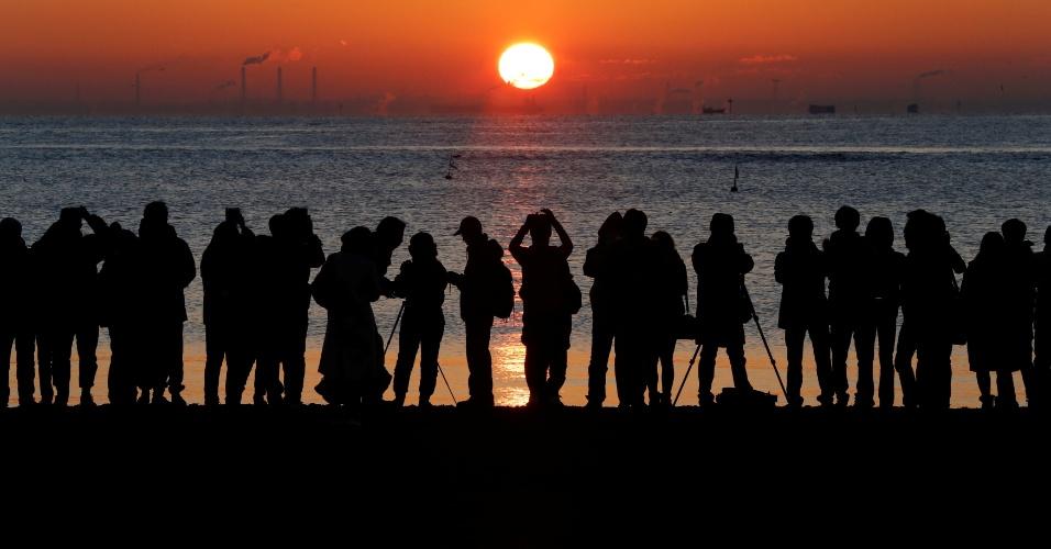 31.dez.2017 - Pessoas assistem ao nascer do sol em 1 de janeiro de 2018 em Tóquio, no Japão