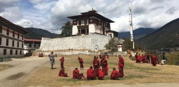 No Butão, homens, mulheres e crianças caminham nas ruas usando as vestimentas típicas