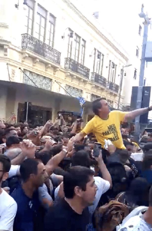 6.set.2018 - Imagem mostra homem encostando um objeto no candidato a presidente Jair Bolsonaro (PSL-RJ)