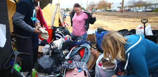Voluntários e evacuados deslocados por incêndio avaliam roupas doadas em um acampamento improvisado perto de um Walmart em Chico, Califórnia