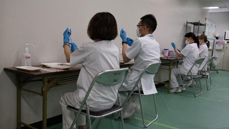 Equipe médica prepara vacinas contra a covid-19 para serem aplicadas em um dos centro de vacinação, em Tóquio - Carl Court/Getty Images