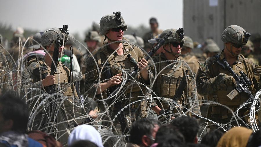20.ago.2021 - Soldados dos Estados Unidos montam guarda atrás de arame farpado na parte militar do aeroporto de Cabul , no Afeganistão - Wakil Kohsar/AFP