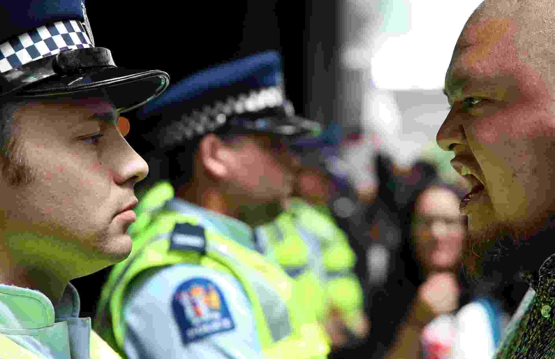 4.fev.2016 - Policiais e manifestante se encaram, enquanto protesto fecha ruas da cidade de Auckland nesta quinta-feira contra o Acordo de Parceria Transpacífico, debatido por ministros neozelandeses nesta quarta. Entre outras medidas, o acordo prevê a eliminação de quase todas as barreiras tarifarias entre os 12 países-membros - entre eles, algumas das maiores economias do mundo, como EUA e Japão - e que respondem por cerca de 40% da economia global - Michael Bradley/AFP