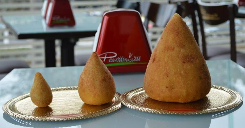 Supercoxinha de um quilo, à direita, comparada ao tamanho tradicional (centro) e à mini coxinha (esquerda)