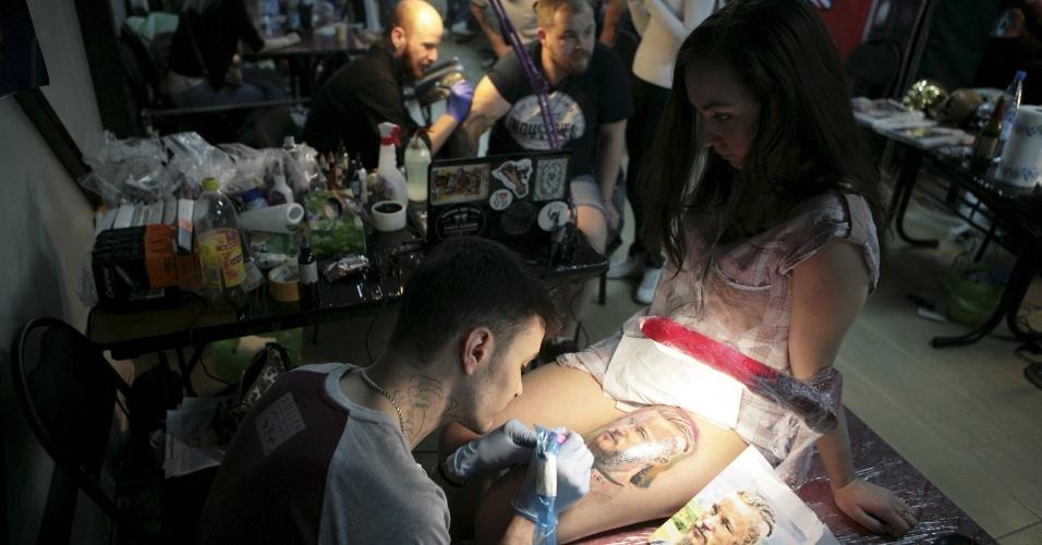 23.abr.2016 - Tatuador desenha na coxa de uma cliente durante o Festival Internacional de Artes de Tatuagens em Xangai, na China