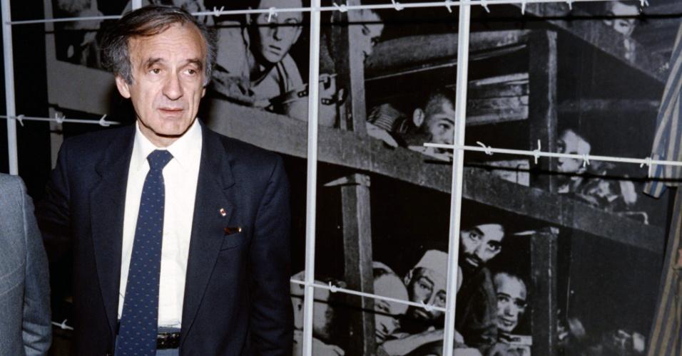 2.jul.2016 - Morreu neste sábado (2) o escritor Elie Wiesel, vencedor do Prêmio Nobel da Paz e sobrevivente do Holocausto. Nesta foto, de dezembro de 1986, Wiesel posa diante de uma imagem dele mesmo (o terceiro a partir da direita na fileira de baixo) feita no campo de concentração de Buchenwald e exposta no Memorial do Holocausto em Jerusalém