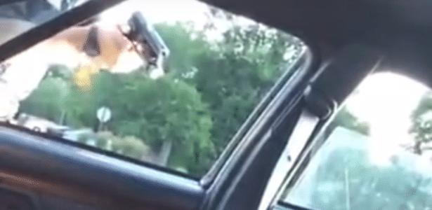 Policial aponta arma para homem negro ferido no interior de carro
