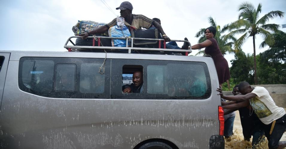 5.out.2016 - Garoto entrega balde de água limpa à mãe, para limpeza da casa inundada na comuna de Leogane, em Porto Príncipe, Haiti, por conta da passagem do furacão Matthew