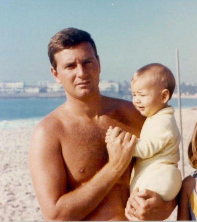 Na praia, Marcelo Crivella carrega o filho, Marcelinho, no colo