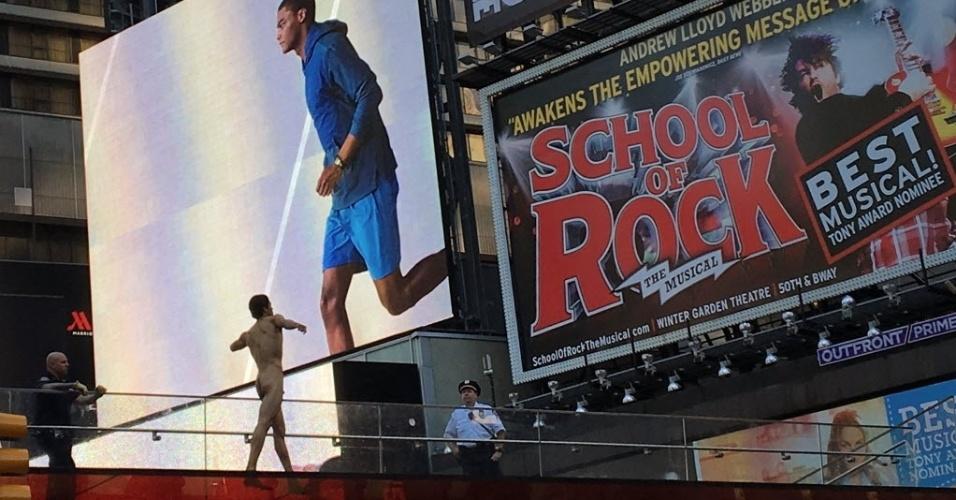 30.jun.2016 - Policiais conversam com um homem pelado que correu pela Times Square, em Nova York (EUA). De acordo com testemunhas, o homem gritou frases sem sentido e perguntou onde estava o pré-candidato republicano dos Estados Unidos, Donald Trump. A polícia levou o homem até o hospital, onde ele tratou de um corte no cotovelo e foi submetido a uma avaliação psiquiátrica