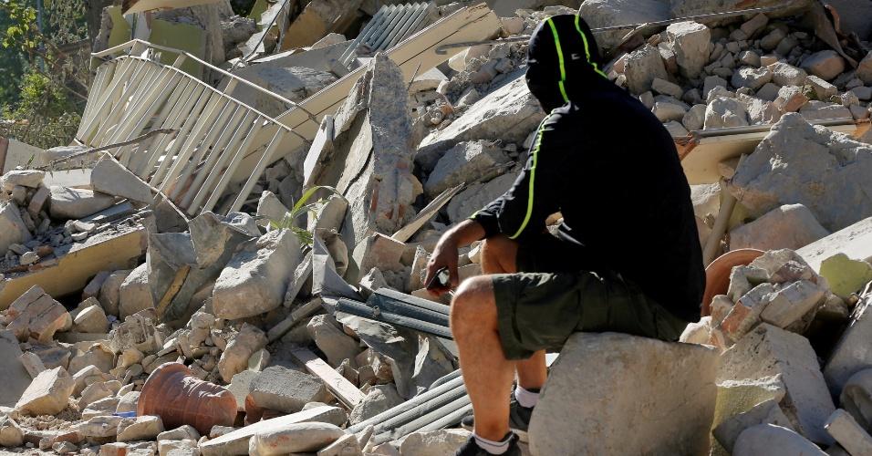 26.ago.2016 - Homem observa destroços deixados pelo terremoto que matou centenas de pessoas em Amatrice, região central da Itália