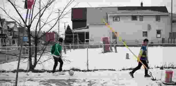 Meninos brincam de jogar bola em bairro em que mais de 500 casas são ocupadas por famílias de refugiados - Nathaniel Brooks/The New York Times