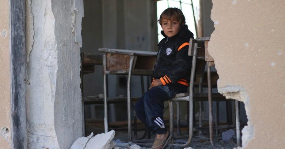 Ahmed, 6, senta diante da carteira de uma sala de aula danificada durante a guerra na cidade síria de Idlib, no norte do país. O menino sonha em se tornar médico quando crescer. Como a escola em que ele estudava foi atacada, Ahmed espera que o pai o leve para estudar no vilarejo vizinho