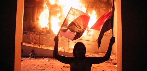 Uma dos centenas de manifestantes que protestaram no Congresso em chamas no Paraguai após aprovação da reeleição
