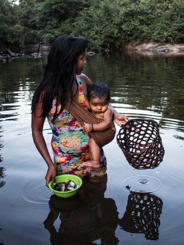 Mulher carrega criança e pesca em área indígena ka'apor, no Maranhão