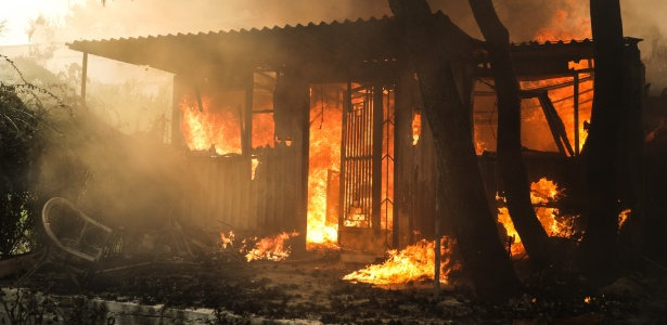 Incêndio florestal atinge casa em Kineta, na Grécia - Xinhua/Lefteris Partsalis