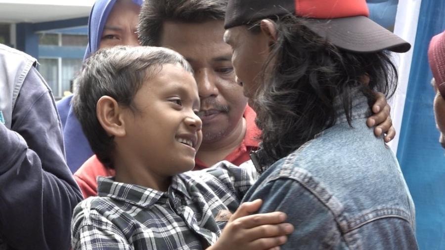 Fikri, que abraça o pai na foto, foi encontrado por uma estudante na beira de uma estrada - Unicef