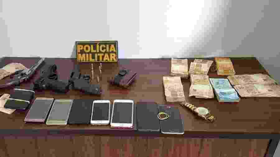 Os R$ 32 mil que haviam sido roubados, celulares de clientes, armas de fogo e um simulacro de pistola foram apreendidos com a dupla - Divulgação/Polícia Militar