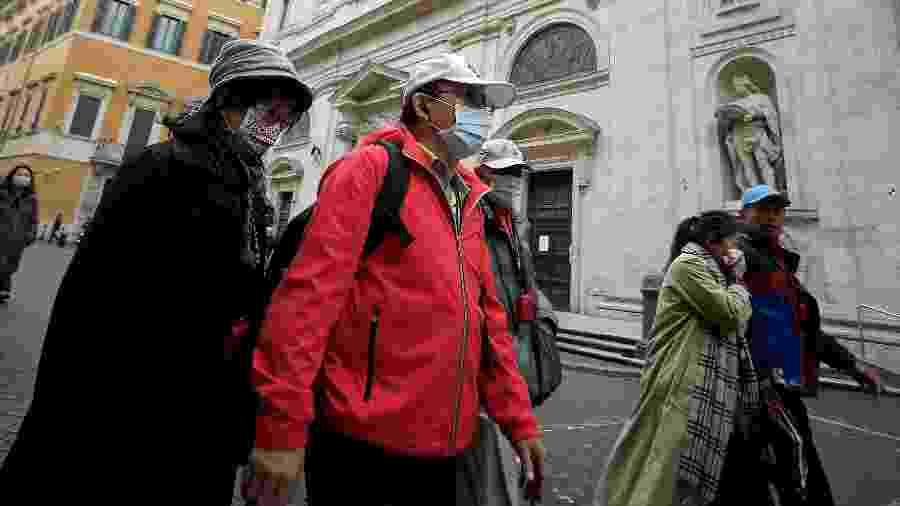 Usando máscaras, turistas asiáticos passam em frente à Igreja San Luigi dei Francesi, em Roma, fechada por conta do coronavírus - Filippo Monteforte/AFP