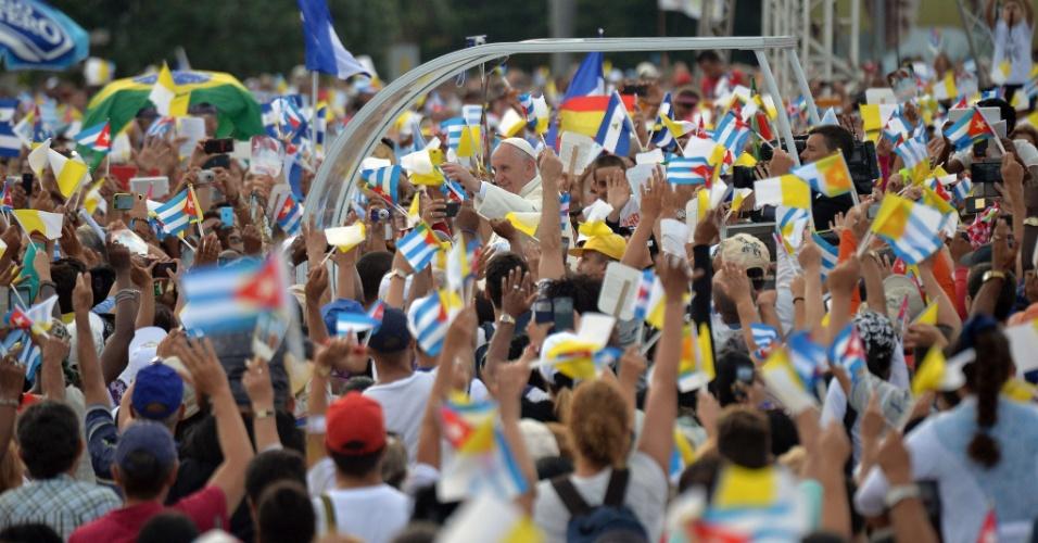 20.set.2015 - Cercado por fiéis que empunham bandeiras de Cuba e de outros países, o Papa Francisco chega na Praça da Revolução, em Havana, Cuba, para celebrar missa, no segundo dia de sua visita a Cuba. Milhares de cubanos se reuniram no local desde a madrugada deste domingo