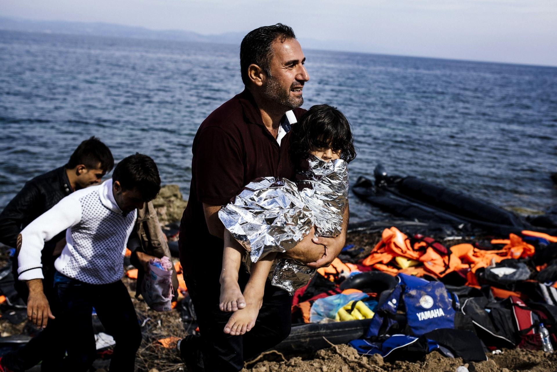 18.out.2015 - Homem carrega criança em cobertor téermico após desembarcar com outros refugiados na ilha de Lesbos, na Grécia. Três crianças e duas mulheres morreram em dois novos naufrágios ocorridos no litoral das ilhas gregas no mar Egeu, quando tentavam entrar na Grécia procedentes da Turquia